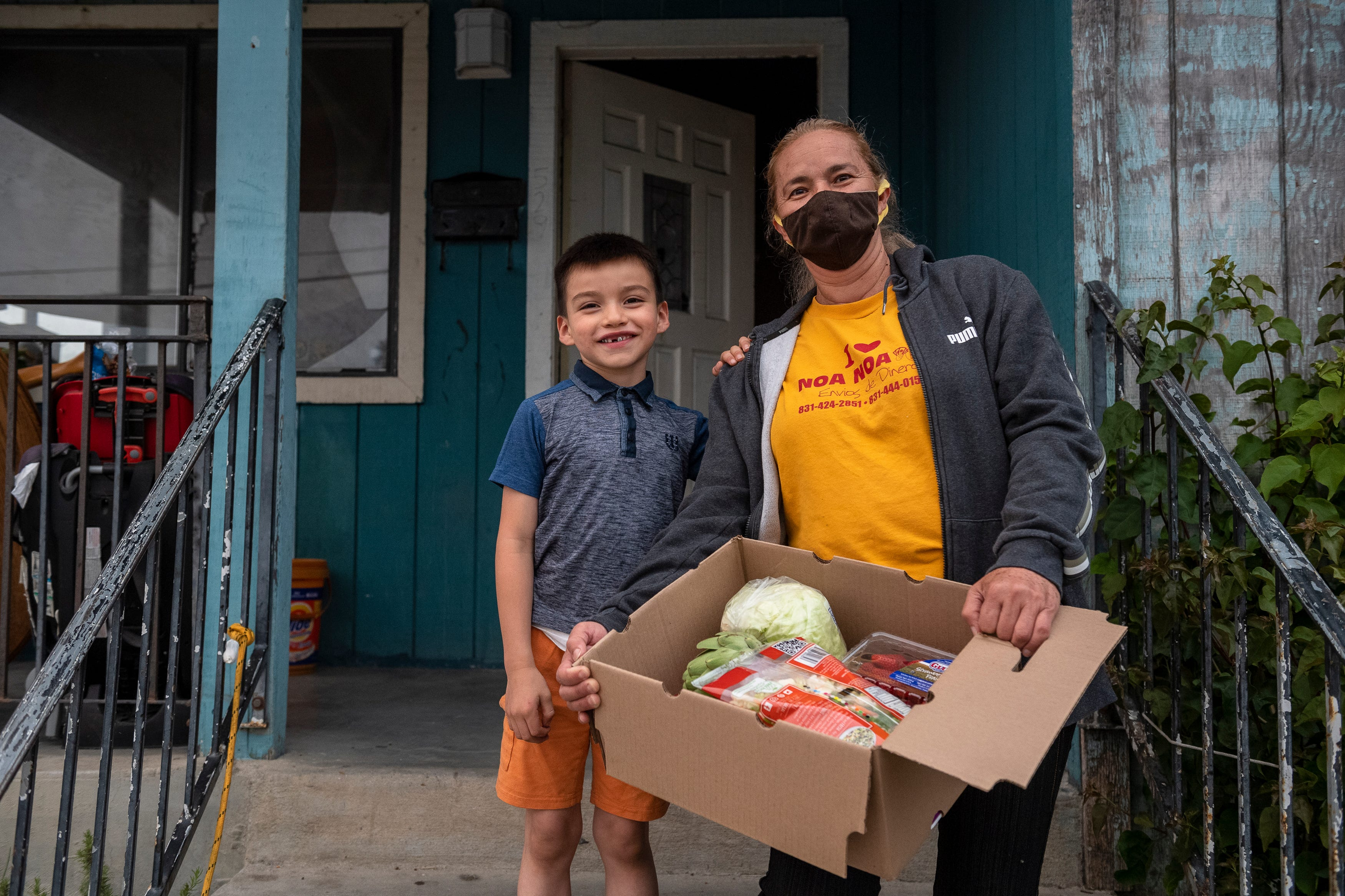 """Kender Ricardez Tobon, left, stands on a door step as he rests his left hand on the shoulder of Eufemia """"Jenni"""" Aguilar. She holds a box filled with different vegetables and fruits donated to them by the Future Citizens foundation, Taylor Farms Center for Learning in Salinas, Calif., on Wednesday, Aug.19, 2020."""