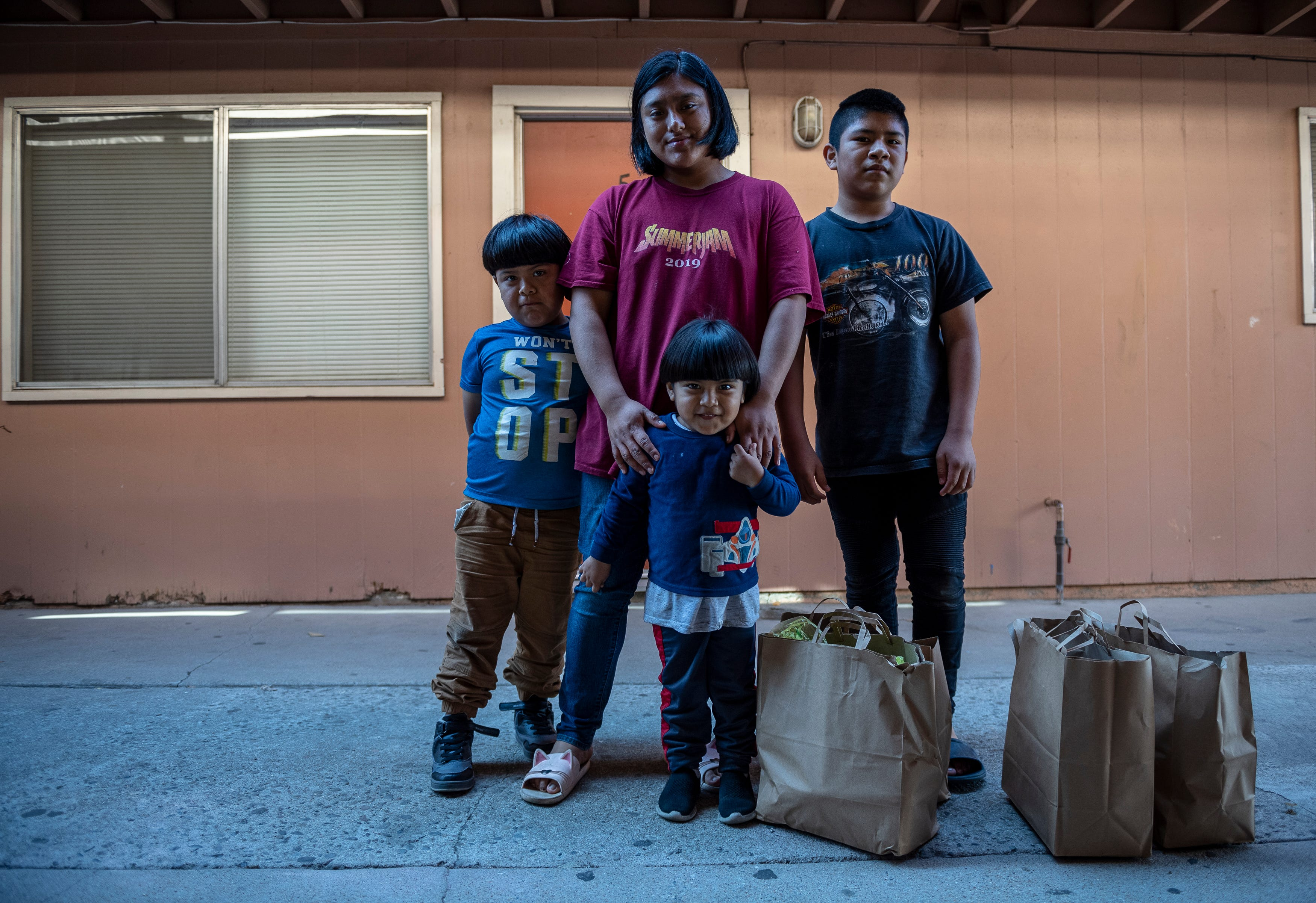 Hugo Salvador, left, Resi Salvador, Jesus Salvador, middle, and Aldo Salvador stand next to a few donated grocery bags full of food products in front of their two-bedroom apartment in north Salinas, Calif., on Saturday, Sept. 26, 2020.