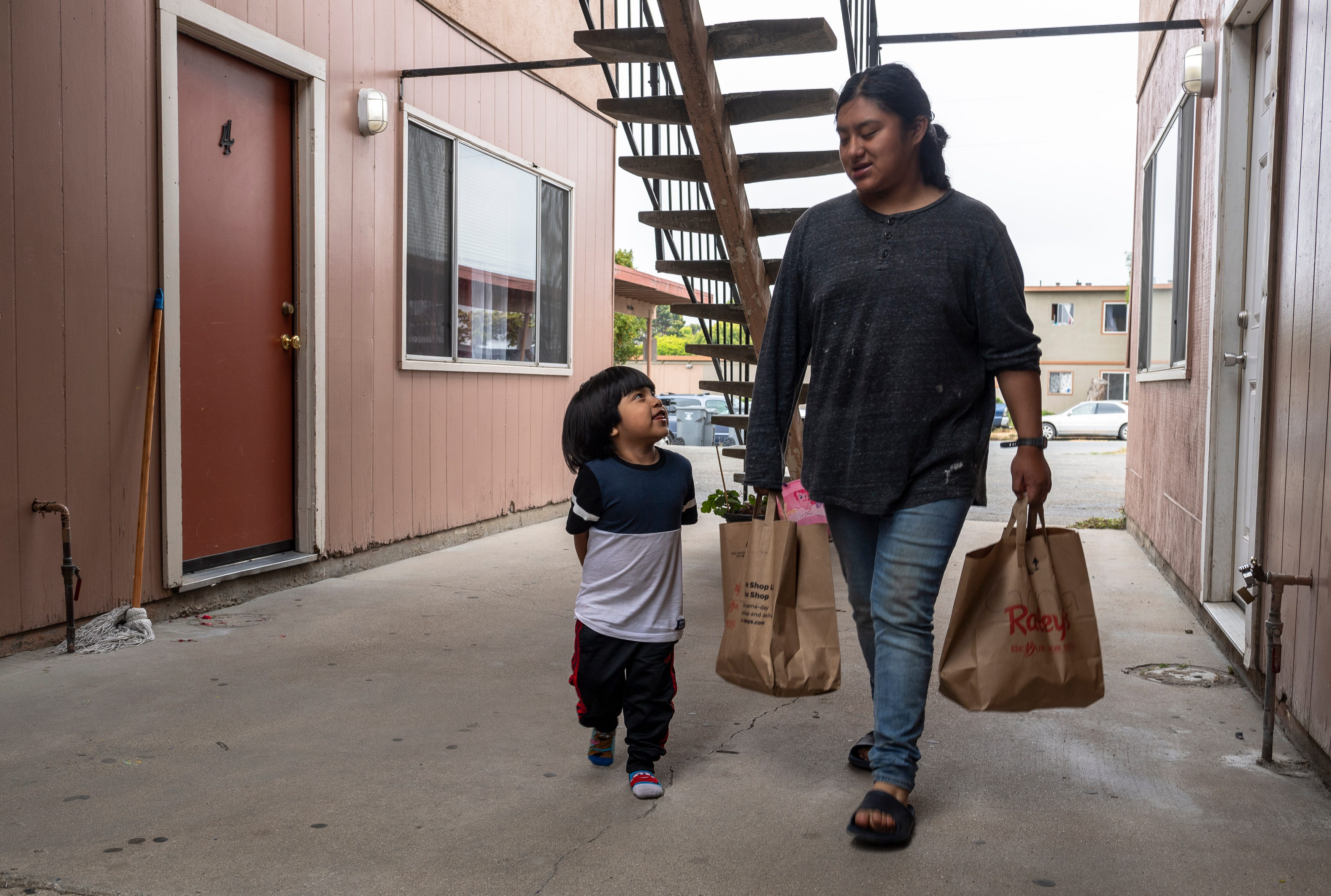 Jesus Salvador, 3, looks up at his sister Resi Salvador, 20, as she carries two bags full of groceries that were donated by a Salinas resident who read her family's story in the Californian in Salinas, Calif., on Saturday, July 18, 2020.