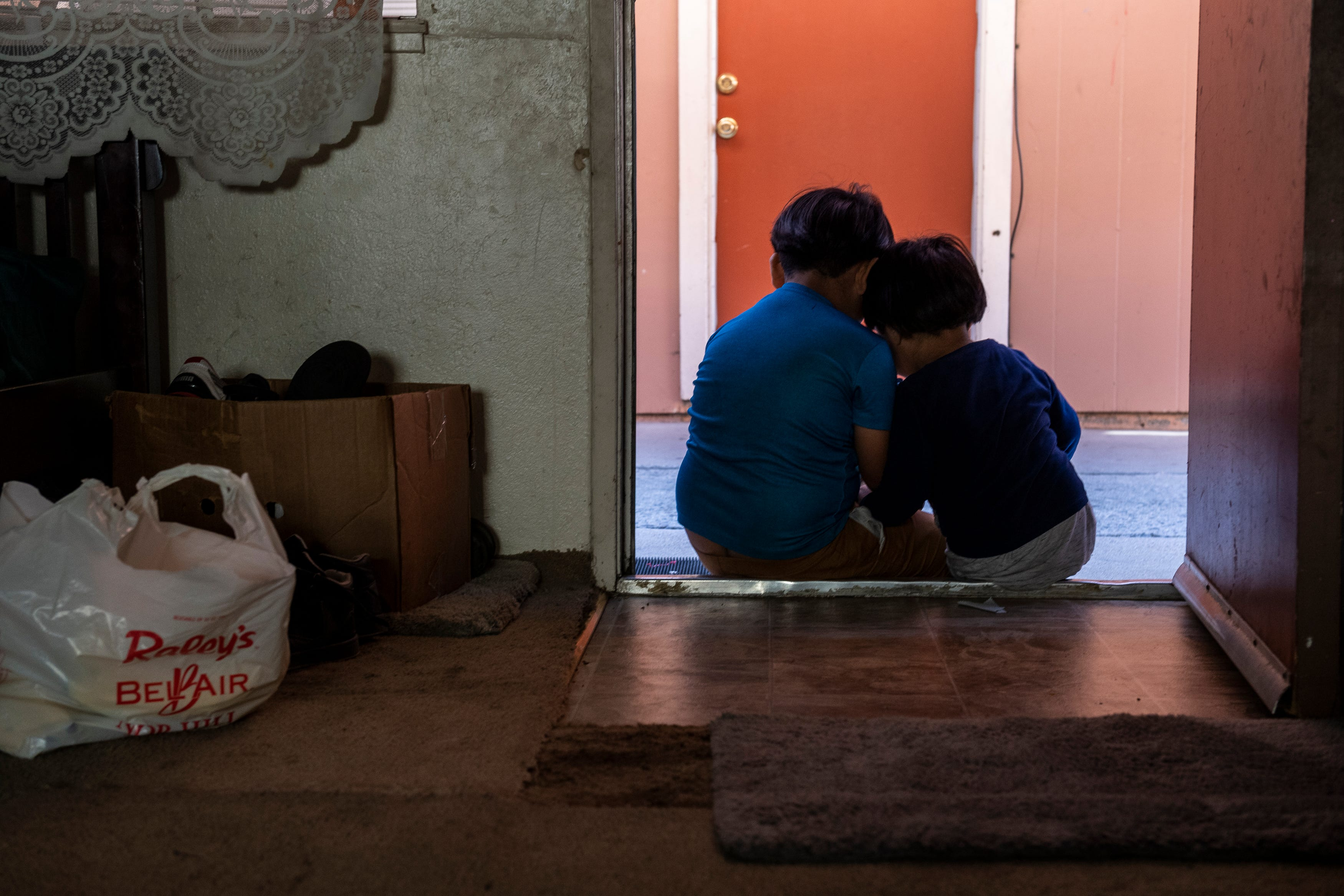 Hugo Salvador, 7, left, sits on a doorstep with his younger brother Jesus Salvador, 3, as they rest their heads on one another in Salinas, Calif., on Saturday, Sept. 26, 2020.