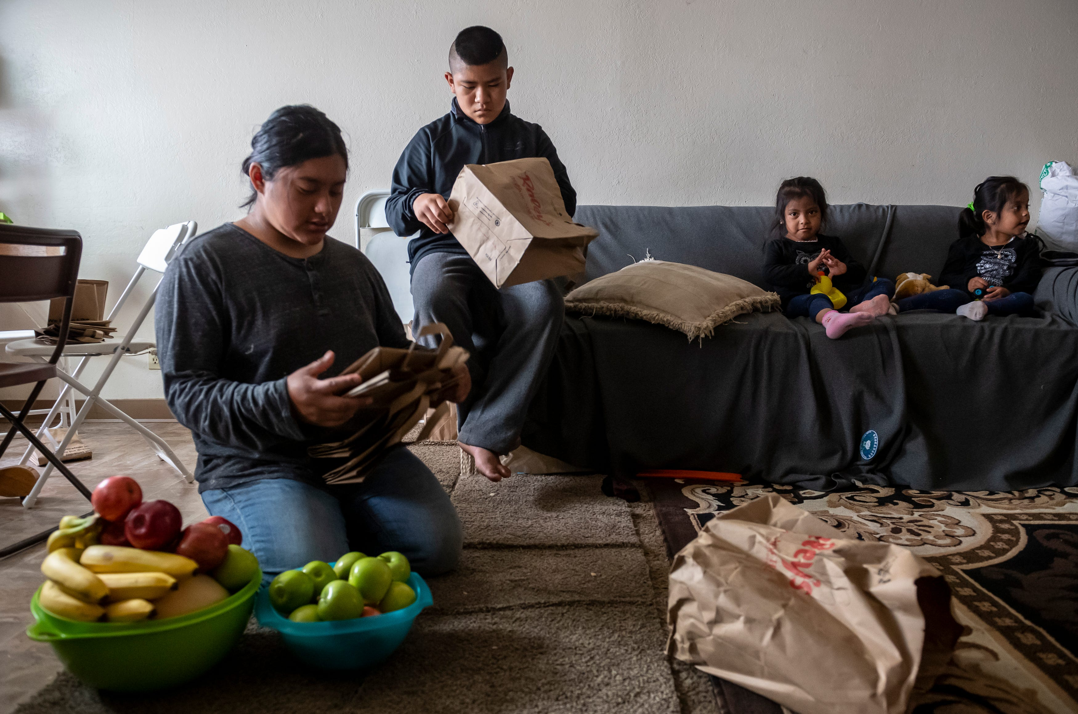 Resi Salvador, 20, left, folds paper grocery bags as her younger brother Aldo Salvador, 11, sits on the couch next to his cousins inside the family's two-bedroom apartment in north Salinas, Calif., on Saturday, July 18, 2020.