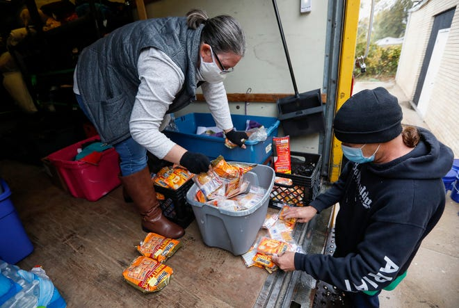 Pastor Christie Love, of the Connecting Grounds, and John Reier go through tubs of hand warmers before heading out to distribute cold weather gear to the homeless on Wednesday, Oct. 28, 2020.