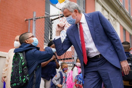 New York Mayor Bill de Blasio, right, greets students as they arrive for in-person classes outside Public School 188 The Island School, Tuesday, Sept. 29, 2020, in the Manhattan borough of New York.