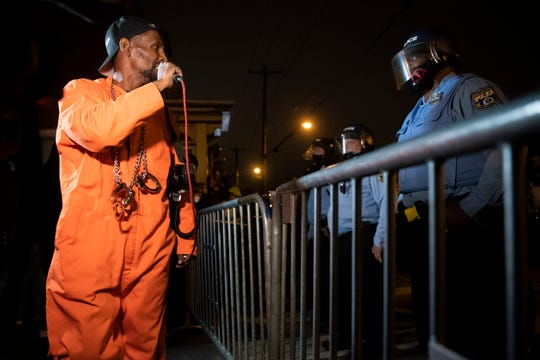 Activist Michael 'OG Law' Ta'Bon speaks to police officers as demonstrators rally in West Philadelphia following the police killing of Walter Wallace Jr. Tuesday, Oct. 27, 2020.