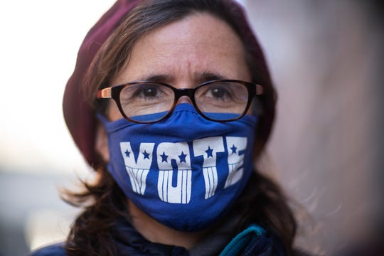 "Cathy Saunders wears a ""VOTE"" mask while standing on line to cast her ballot in Providence, Rhode Island."