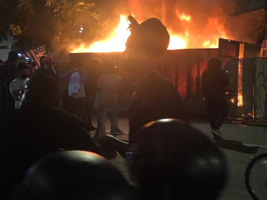A man walks past a dumpster fire as Dodgers fans celebrate the team's World Series in Los Angeles.