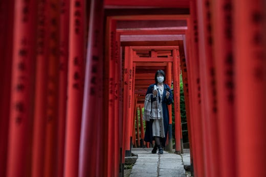A woman wearing a face mask walks under torii gates (traditional Japanese gates) as she visits a Shinto shrine on October 28, 2020 in Tokyo, Japan. The Tokyo Metropolitan Government reported 171 new cases of Covid-19 coronavirus today.