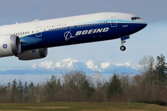 A Boeing 777X airplane takes off on its first flight with the Olympic Mountains in the background at Paine Field in Everett, Wash., in this Jan. 25, 2020, file photo .  Boeing will cut more jobs as it continues to lose money and revenue during a pandemic that has smothered demand for new airline planes. The company said Wednesday, Oct. 28,  that it expects to cut its workforce to about 130,000 employees by the end of next year, down 30,000 from the start of this year.