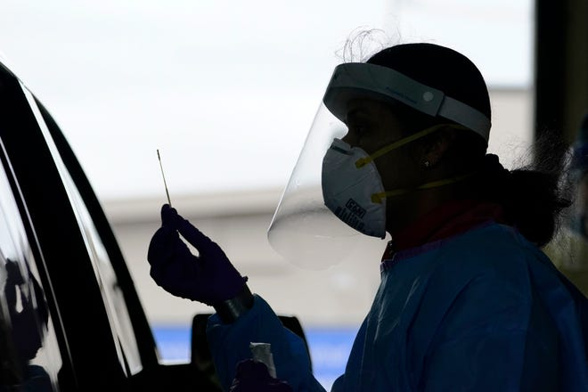 University of Washington research coordinator Rhoshni Prabhu holds up a swab after testing a passenger at a free COVID-19 testing site in Seattle on Oct. 23.