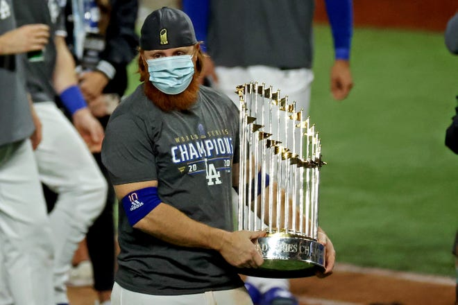 Justin Turner holds the World Series trophy on the field.