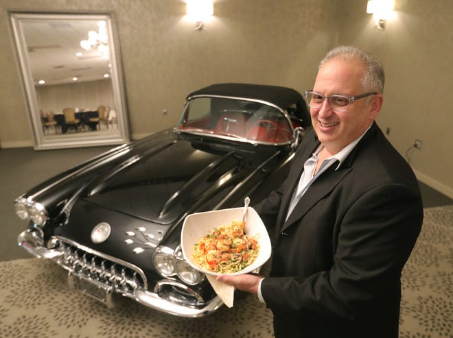 FAT'S in the Valley owner Frank Todaro holds a bowl of linguini with shrimp as he stands next to a 1960 Corvette Roadster parked in his 7,000-square-foot dining area in Akron.