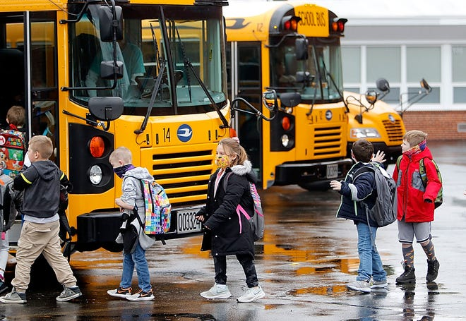 Students board buses at the end of the school day at Edison Elementary School last October. The CDC's updated guidance now requires masks be worn on public transportation, which the agency said includes school buses.