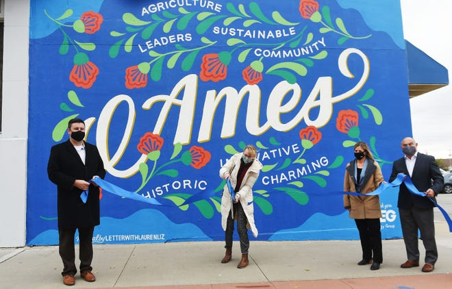 Artist Lauren Gifford cuts the ribbon for the official unveiling of the mural in the ribbon-cutting ceremony at Kellogg Avenue in downtown Ames Thursday, Oct. 29, 2020, in Ames, Iowa.