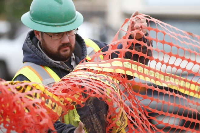 City of Brownwood utility worker Tanner Brown helps place safety netting Wednesday morning around a pit where a sewer line is being replaced in the alley next to Trans Texas Tire.  Despite working in the chilly weather, utility crew workers said moving around while completing their tasks kept them from being cold.
