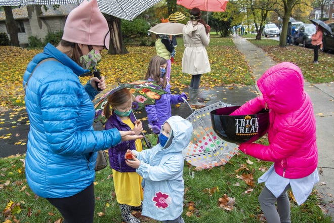 Clinton Elementary School students wait outside their homes on East North Broadway as teachers and faculty walk through the neighborhood handing out candy a few days before Halloween in 2020.
