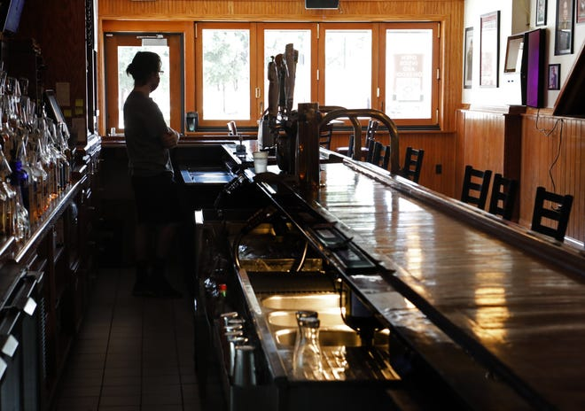 R.J. Oberle night manager at the Varsity Club on Lane Avenue waits for customers on Aug. 11. Bars and restaurants in Columbus and around the state will be eligible for new relief programs meant to get them through the pandemic.