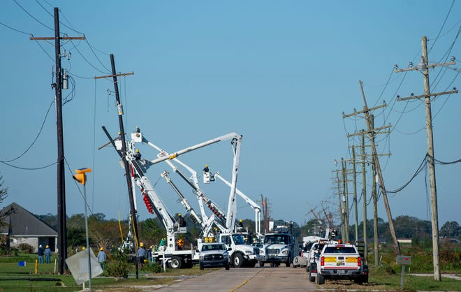 Work crews repair power lines south of Houma following Hurricane Zeta on Thursday.