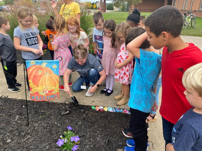 Julie Childs' kindergarten students add their painted rocks to the MWES rock garden.