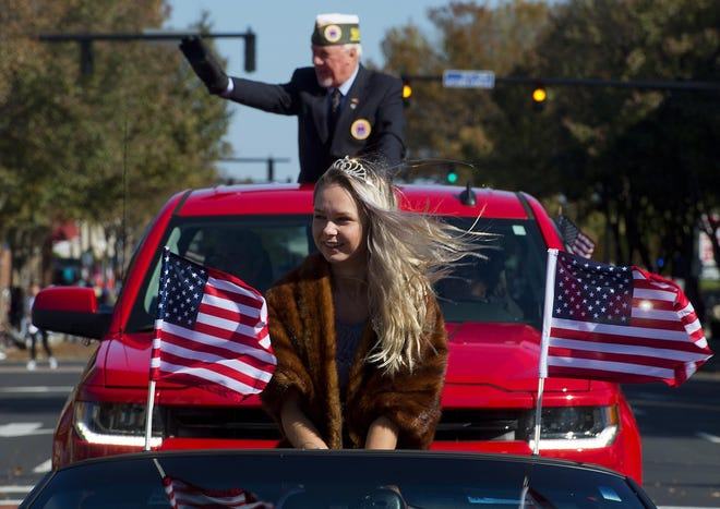 The Davidson County Veterans Day Parade has been canceled. In this file photo from the 2018 parade, a gust of wind whips the American flags and the hair of AMVETS Post 13 queen Kayce Revelle as Post 13 Commander Danny Brewer waves to spectators during the parade in Lexington.