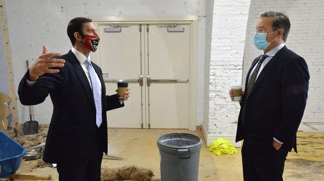 John Persinger, left, CEO of the Erie Downtown Development Corp., leads a tour of EDDC properties with Jonathan Tower, managing partner of Arctaris Impact Investors, on Thursday in Erie. Arctaris is investing $30 million in EDDC projects.