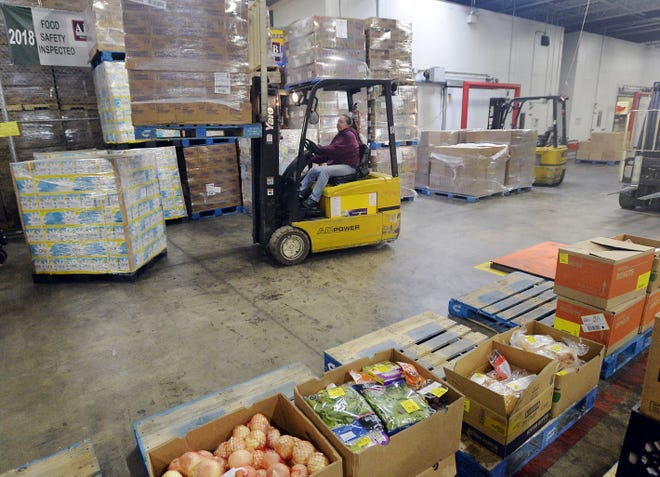 An employee helps load food at the Second Harvest Food Bank in this October 2018 photo.