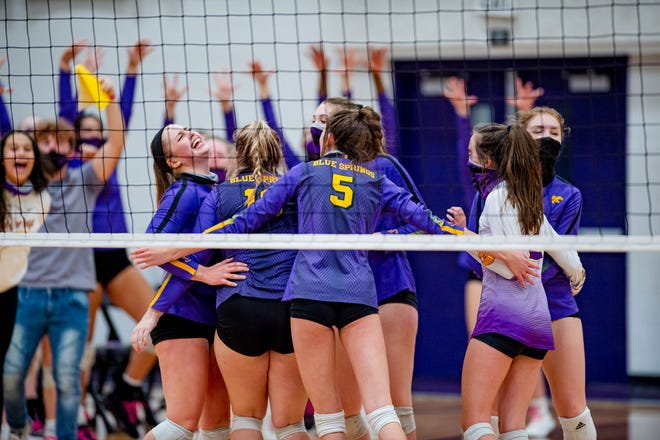 Blue Springs players Lily Letchworth, left, and Maya Fergerson (5) celebrate with teammates after defeating Blue Springs South in the Class 5 District 14 championship match Wednesday night. The Wildcats won in three sets to advance to Saturday's sectional playoff against Park Hill.