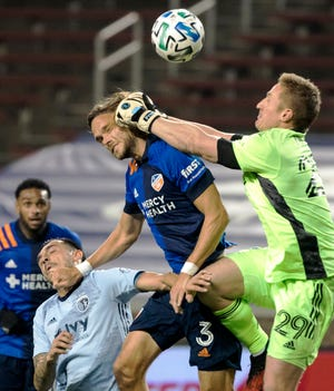 Sporting Kansas City goalkeeper Tim Melia, right, collides with FC Cincinnati defender Tom Pettersson (3) while trying to punch away the ball in front of the goal in Wednesday's MLS match at Nippert Stadium in Cincinnati. Melia made two saves to become Sporting KC's all-times saves leader and lead his team to a 1-0 victory.