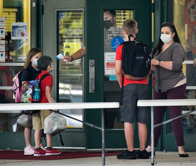 Students have their temperatures taken at Beauclerc Elementary School on the first day of classes Aug. 20.