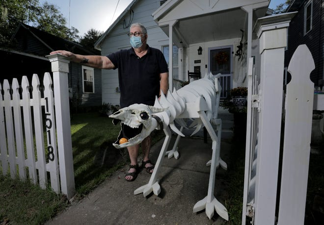 Springfield resident Lee Fifield poses with Puff, his candy dispensing dragon skeleton that he built to distribute candy in his neighborhood's socially distanced Halloween celebration.