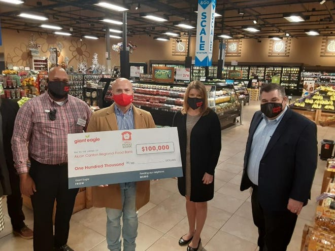 Giant Eagle made a corporate donation of $100,000 Thursday morning to the Akron-Canton Regional Foodbank. (Left to right) Terrell Kemp with Giant Eagle; Dan Flowers, president and CEO of Akron-Canton Regional Foodbank; Renee Dawson-Pilat with Giant Eagle; and Far Right: Brian Ferrier with Giant Eagle. (IndeOnline.com / Steven M. Grazier)