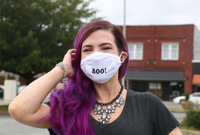 Allie Cantu poses in downtown Kinston with a BB Apparel Alterations Halloween-themed face mask, which the CDC recommends people wear during the Halloween holiday instead of costume masks amid the COVID-19 pandemic. [Brandon Davis/Kinston Free Press]