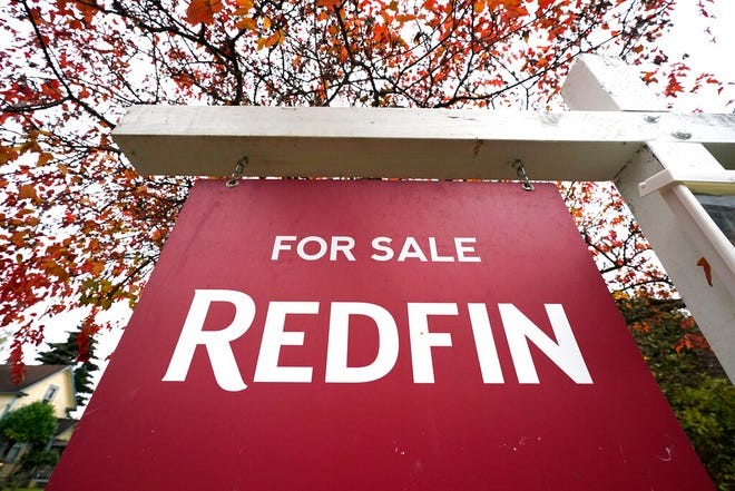 """A Redfin """"for sale"""" sign stands in front of a house Wednesday, Oct. 28, 2020, in Seattle. Several fair housing organizations accused Redfin of systematic racial discrimination in a lawsuit Thursday, saying the online real estate broker offers fewer services to homebuyers and sellers in minority communities, a type of """"digital redlining"""" that has depressed home values and exacerbated historic injustice in the housing market."""