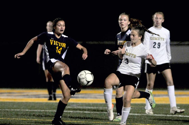 Victor's Alaina Andre (14) puts a touch on the ball as Rush-Henrietta's Brooke Cicoria defends during Wednesday's match.