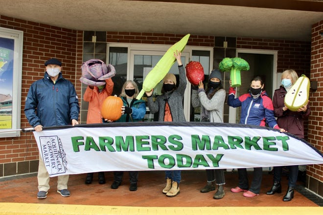 ACT board and staff members gathered in the rain Wednesday to have a little fun with vegetables outside of the Gateway Visitor's Center, the Aquidneck Growers' Market new winter home.