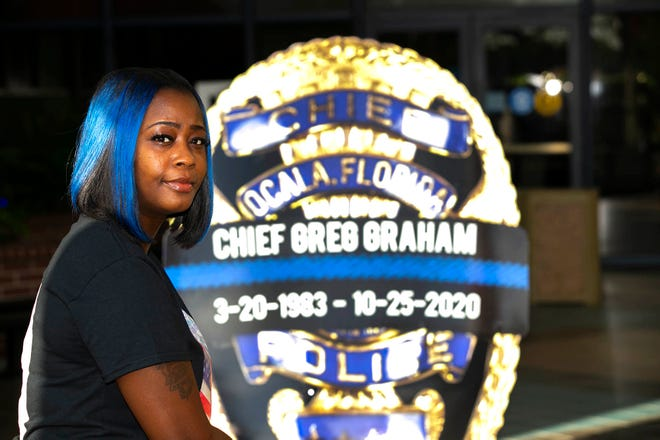 Tocara Davis sits outside the Ocala Police Department headquarters on Wednesday near the tribute sign for Police Chief Greg Graham, who died Sunday in a plane crash. Davis says Graham was instrumental in turning her life around and helping guide her through the process to achieve her goal of becoming a police officer. Davis says she will honor Graham by continuing to work toward her goal.
