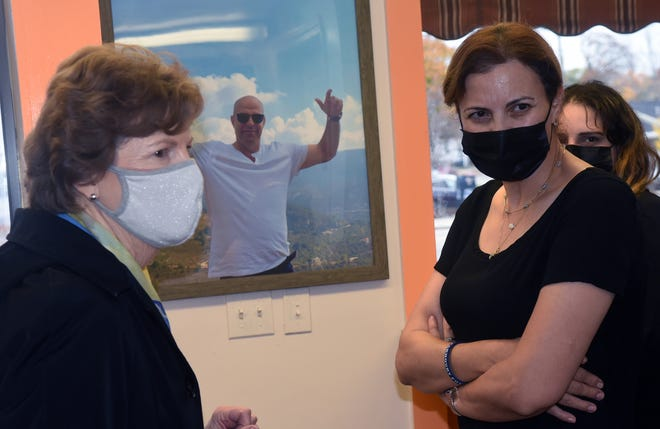 A photograph of the late Amer Fakhoury hangs on the wall of the Little Lebanon To Go restaurant in Dover Thursday as Sen. Jeanne Shaheen, left, and Fakhoury's widow, Michelle, listen to other family members.
