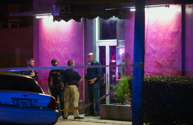 West Palm Beach police talk with a man outside Rain Gentlemen's Club as they investigate the shooting of two security officers before dawn Thursday, Oct. 29, 2020. Police say the security officers were transported to the hospital with non-life threatening injuries.