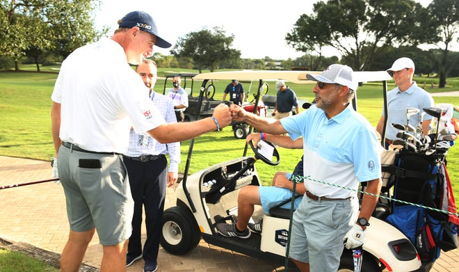 Ernie Els (left) fist bumps Jesse Singh, the CEO of AZEK, the parent company of TimberTech, during Thursday's Pro-Am at Broken Sound. Scott Halleran/Special to The Post