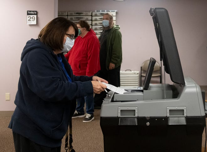 Rose Buchina, of Aurora, returns her ballot during early in-person voting at the Portage County Board of Elections in Ravenna.