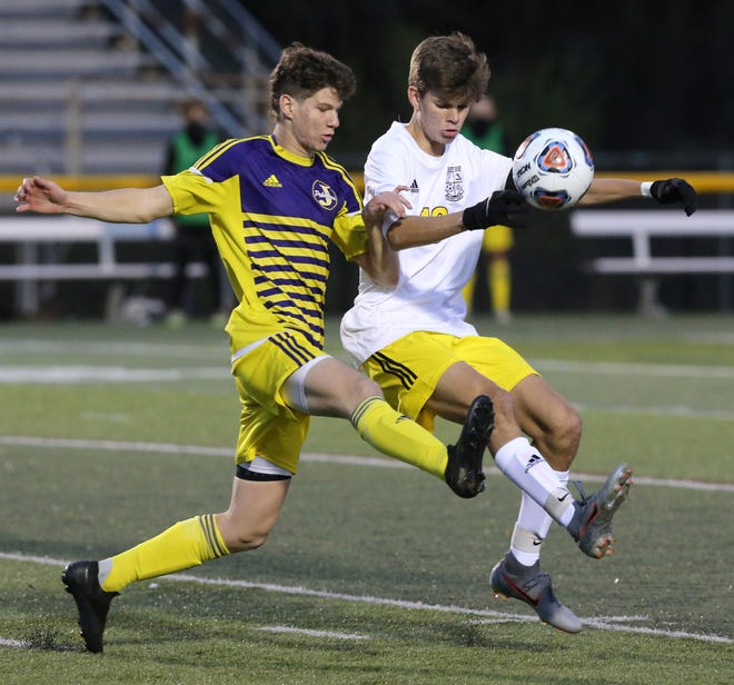 Ryan Buckler (left) of Jackson fights for control of the ball with Drew Tyler (right) of Perry during their Division I district semifinal game on Wednesday.