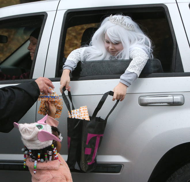 Milania Hiple holds out her bag for a treat in Stadium Park for Trunk for Treat in Canton on Thursday.