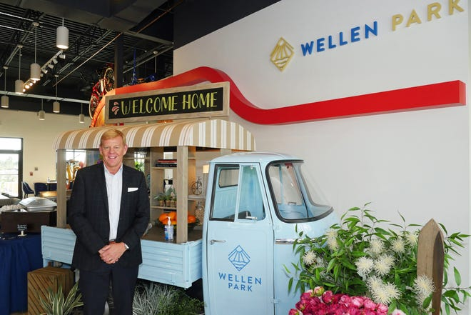 Rick Severance, president of Mattamy Homes' Wellen Park Division, poses in front of the reception desk, which is a converted Piaggio Apé service cart, at the Wellen Park Welcome Center. Use of the cart was inspired by the planned Downtown Wellen food truck area and meant to be a comfortable place to have a conversation.