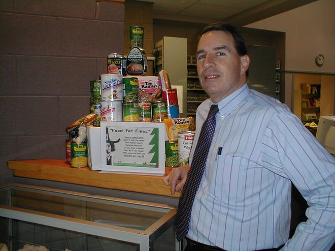 """Pender County librarian Mike Taylor circa 2005 with cans as part of a """"Food for Fines Drive"""" when Taylor decided to allow people to bring in canned goods to pay off their fines. The food was donated to two county food banks."""