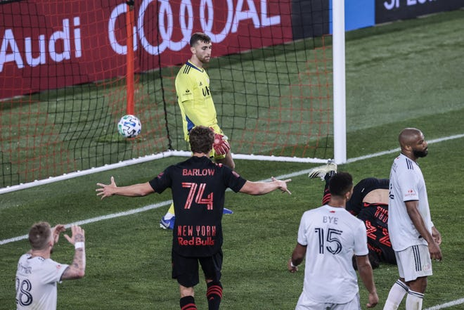 Revolution goalkeeper Matt Turner reacts after allowing a goal by midfielder Aaron Long,  not pictured, in front of forward Tom Barlow (74) and midfielder Brandon Bye (15) during the second half at Red Bull Arena in Harrison, New Jersey.