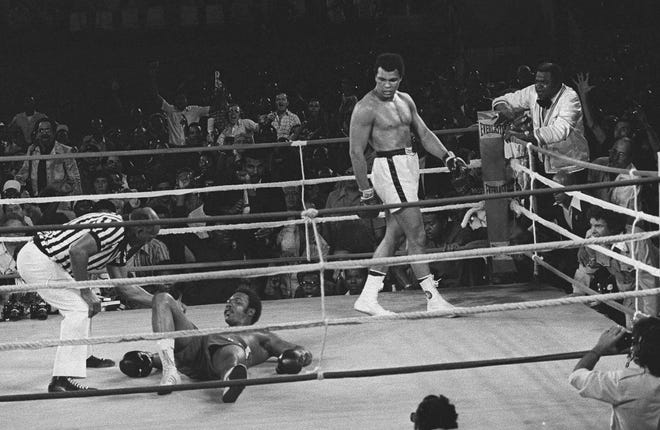 Referee Zack Clayton counts out George Foreman as Muhammed Ali looks on in the 8th round of their title bout in Kinshasa, Zaire, in this Oct. 30, 1974 photo.
