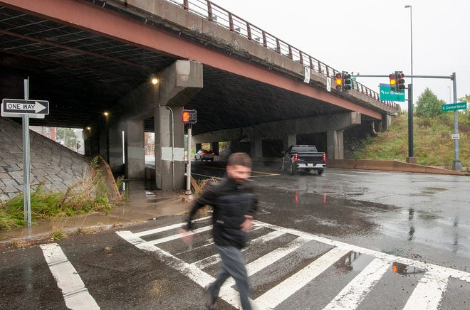 A man runs in the rain after passing under the bridge that carries Interstate 290 west over East Central Street in Worcester Tuesday.