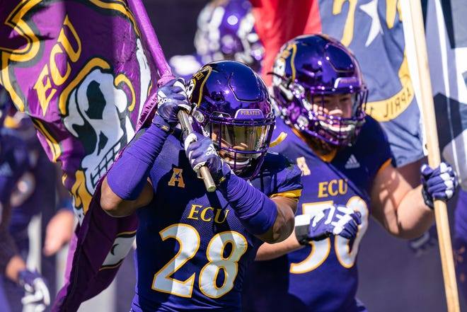 East Carolina Pirates defensive back Ahonore Varner (28) carries out the team flag during an NCAA football game on Saturday, Oct. 17, 2020, in Greenville, N.C. (AP Photo/Jacob Kupferman)