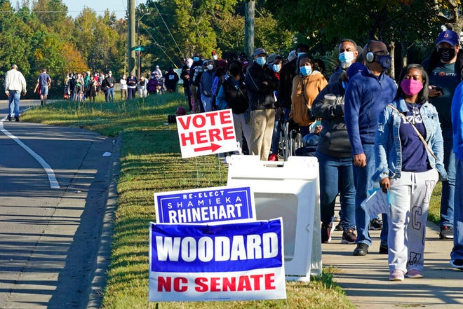 Early voters form a long line while waiting to cast their ballots at the South Regional Library polling location in Durham, N.C., Thursday, Oct. 15, 2020. Some waited almost 3 hours to vote. (AP Photo/Gerry Broome)