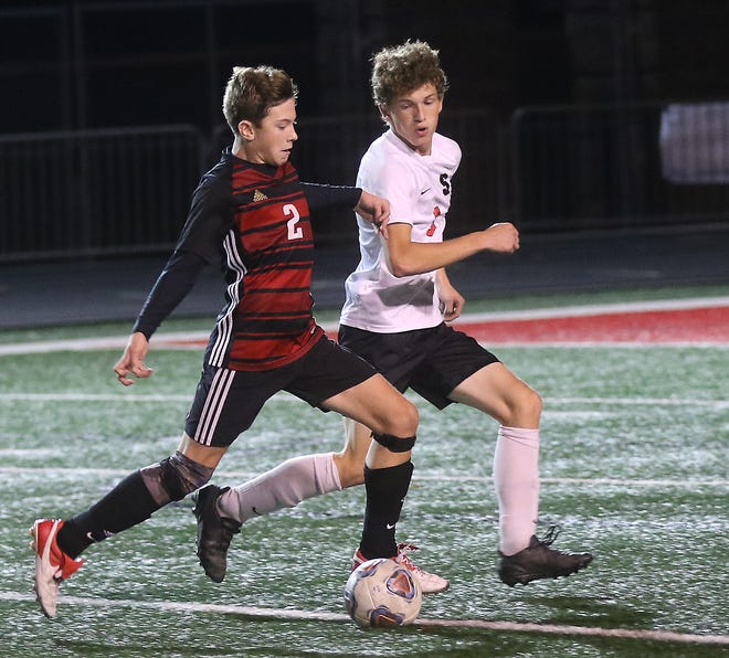 New Philadelphia's Logan Garner battles Steubenville's Josh Zeiler in the Division II semifinal  soccer match Wednesday.