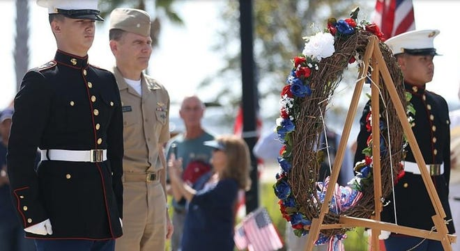 NSAPC Cmdr. Kevin Christenson is escorted by Mosley High School Marine Corps JROTC students during a Laying of the Wreath ceremony at the Panama City Marina on Nov. 11, 2019.